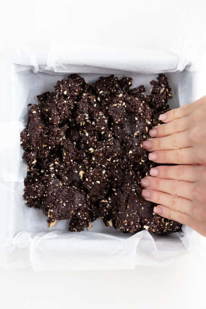 hands pressing raw brownie dough into a square baking pan