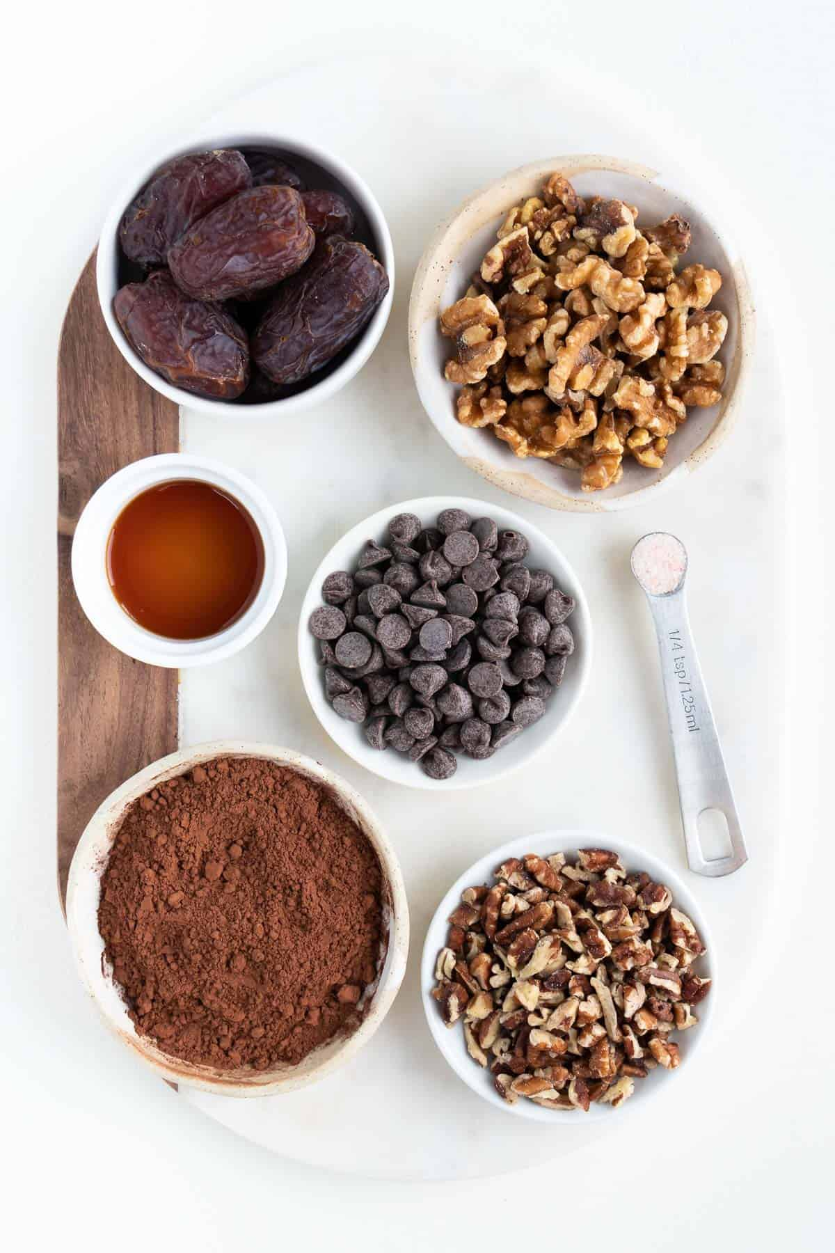 wood and marble cutting board topped with bowls of medjool dates, chocolate chips, walnuts, pecans, maple syrup, and cocoa powder.