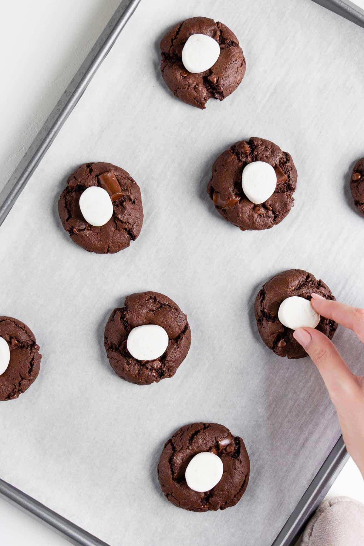 a hand pressing marshmallows on top of vegan double chocolate chunk cookies