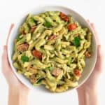 two hands holding a large white bowl of vegan pesto cavatappi pasta
