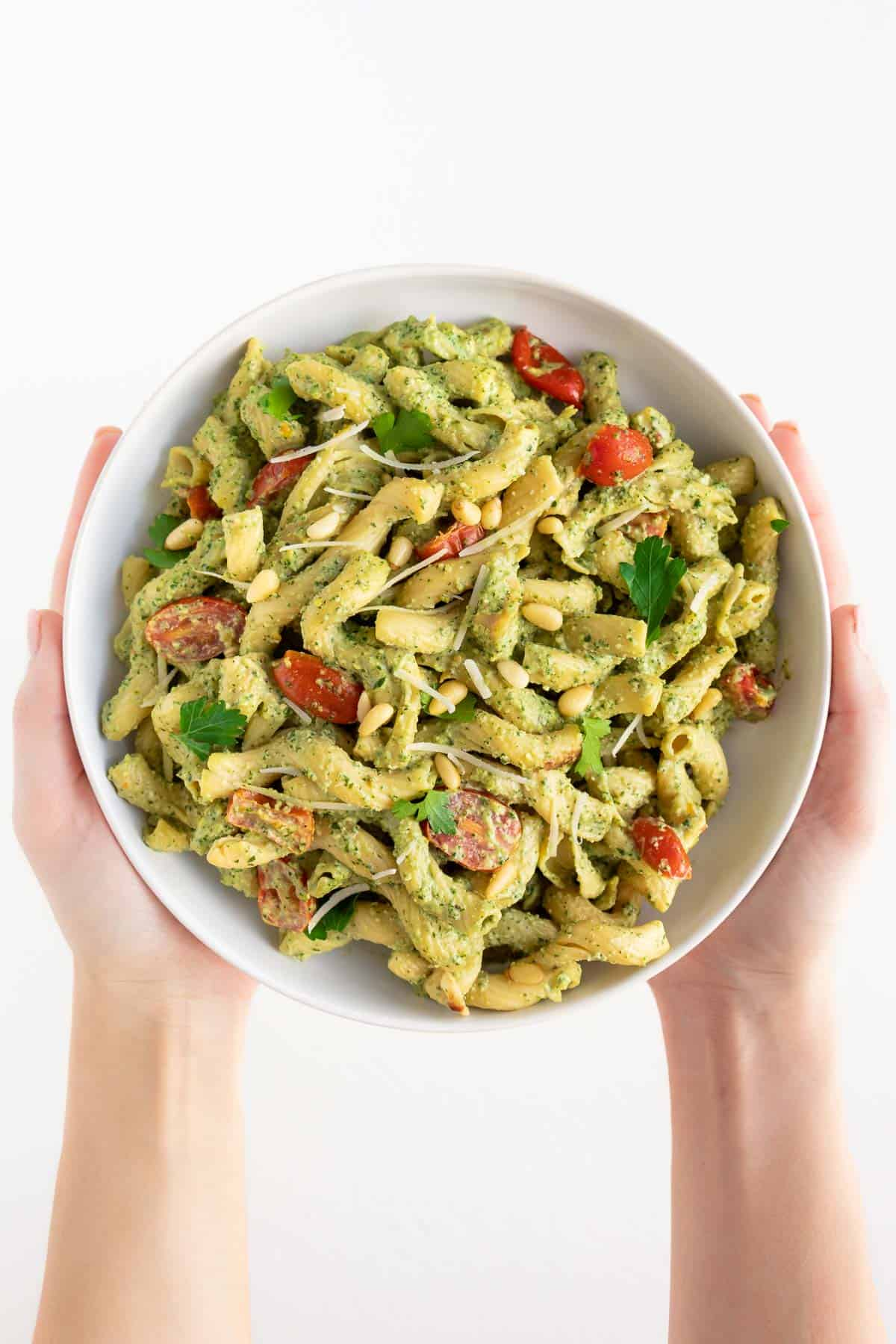 two hands holding a bowl of vegan pesto cavatappi pasta