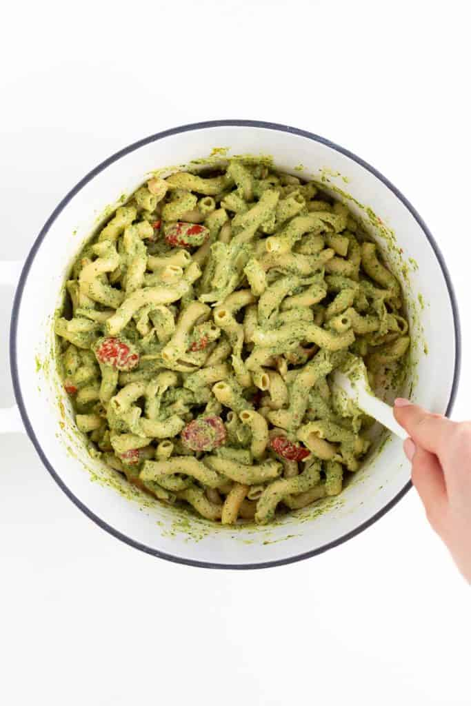 hand holding a white spatula mixing vegan pesto cavatappi in a white sauce pot