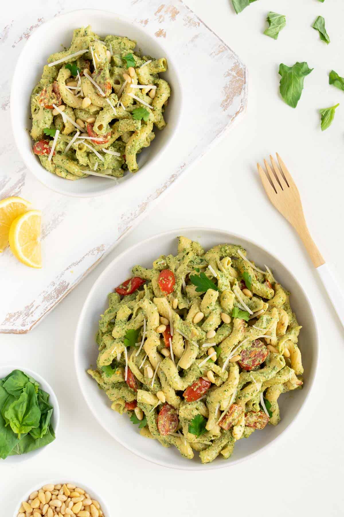 two white bowls filled with vegan pesto cavatappi pasta alongside a small bowl of basil leaves, lemons, a wooden fork, and pine nuts