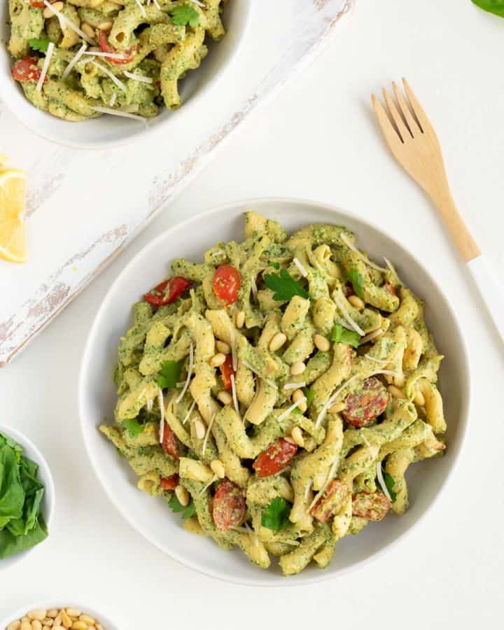 two bowls of vegan pesto cavatappi pasta surrounded by fresh basil, pine nuts, and a wooden fork
