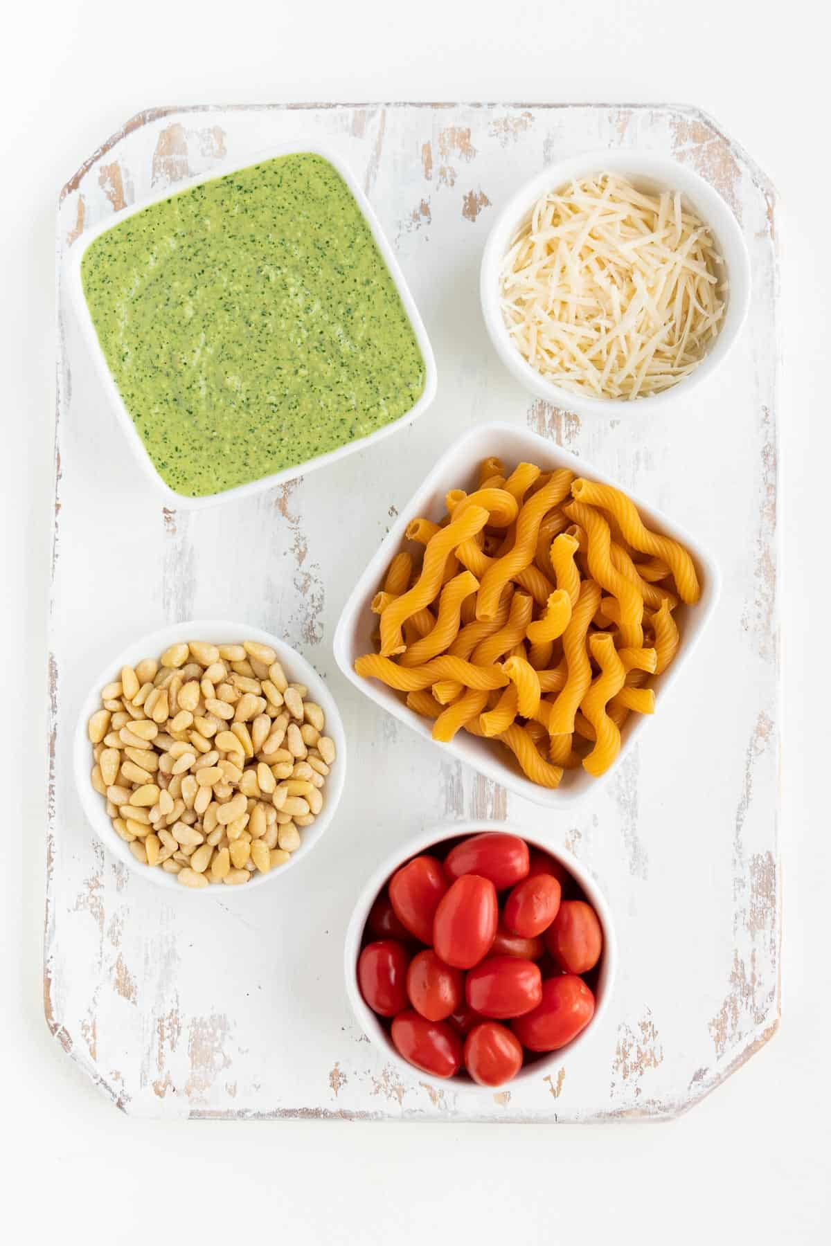 distressed white wood cutting board topped with small bowls of pesto sauce, vegan parmesan cheese, pine nuts, cherry tomatoes, and cavatappi pasta shells