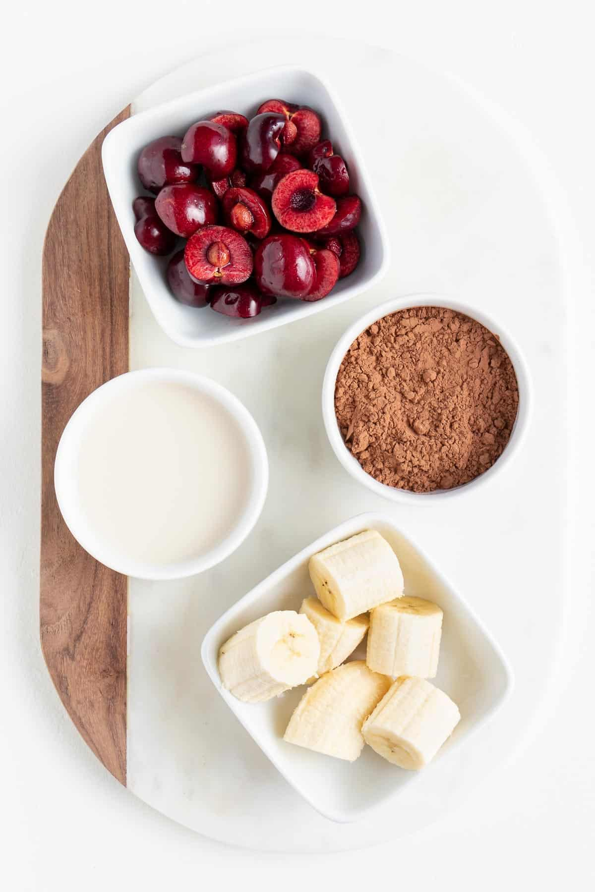 sliced bananas, cocoa powder, almond milk, and berries inside bowls on a white marble board