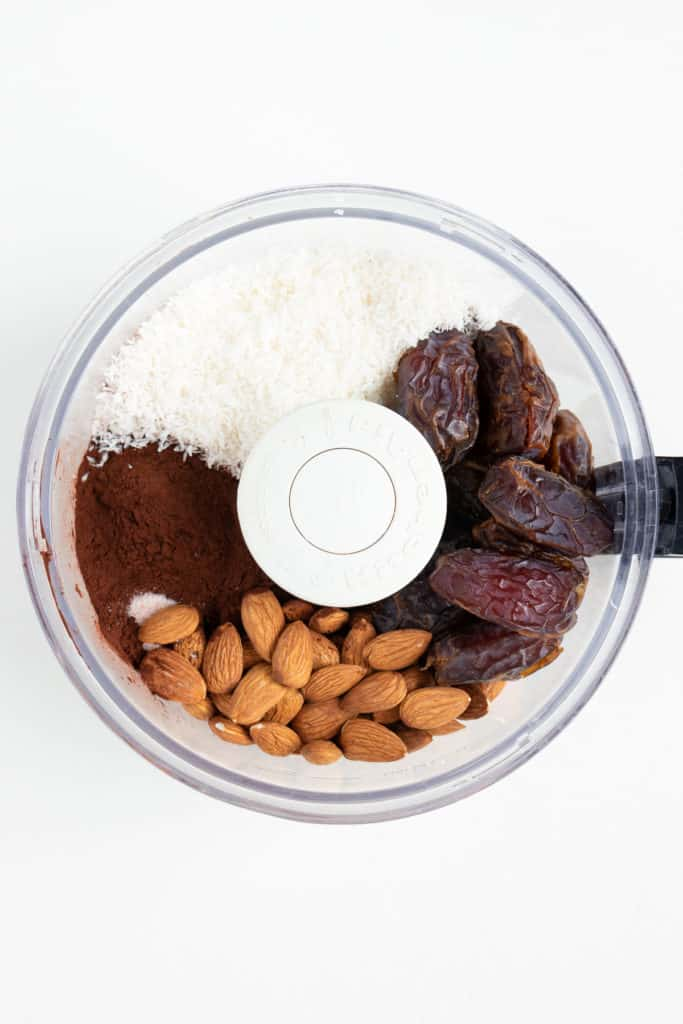 medjool dates, raw almonds, cacao powder, and desiccated shreds inside a food processor