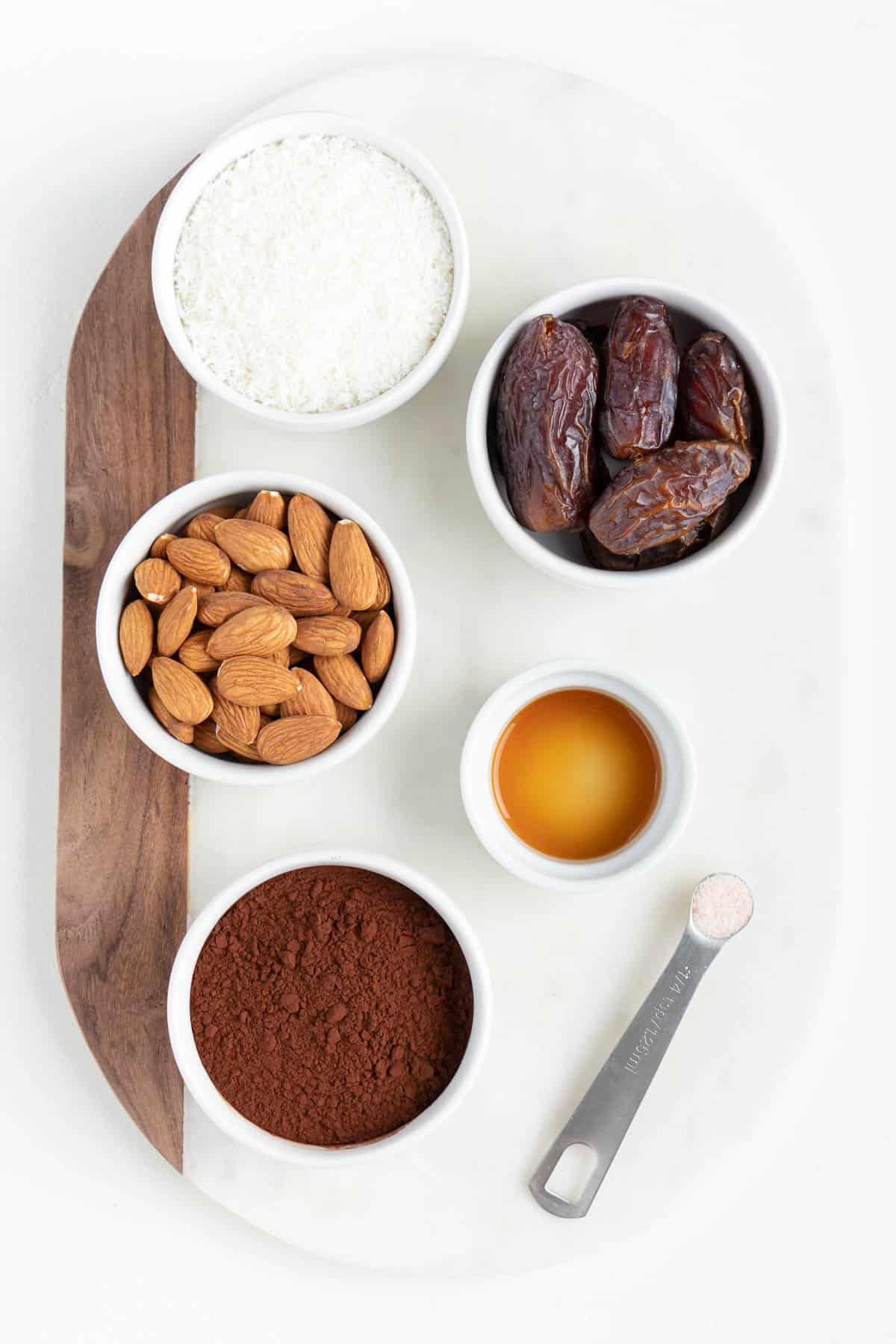 small white bowls filled with raw almonds, medjool dates, cacao powder, vanilla extract, and a teaspoon of salt on a marble board
