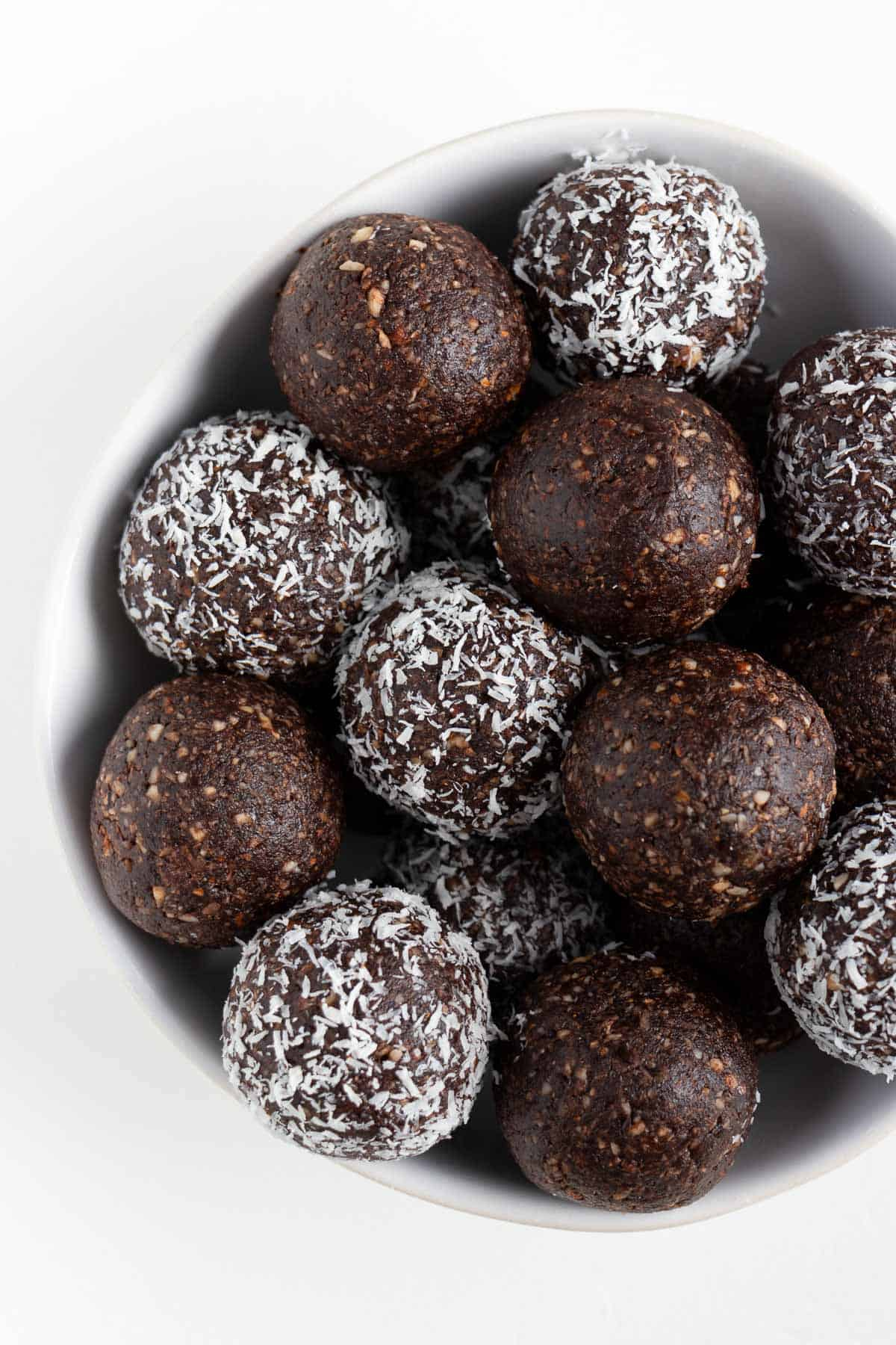 chocolate coconut energy balls inside a white bowl