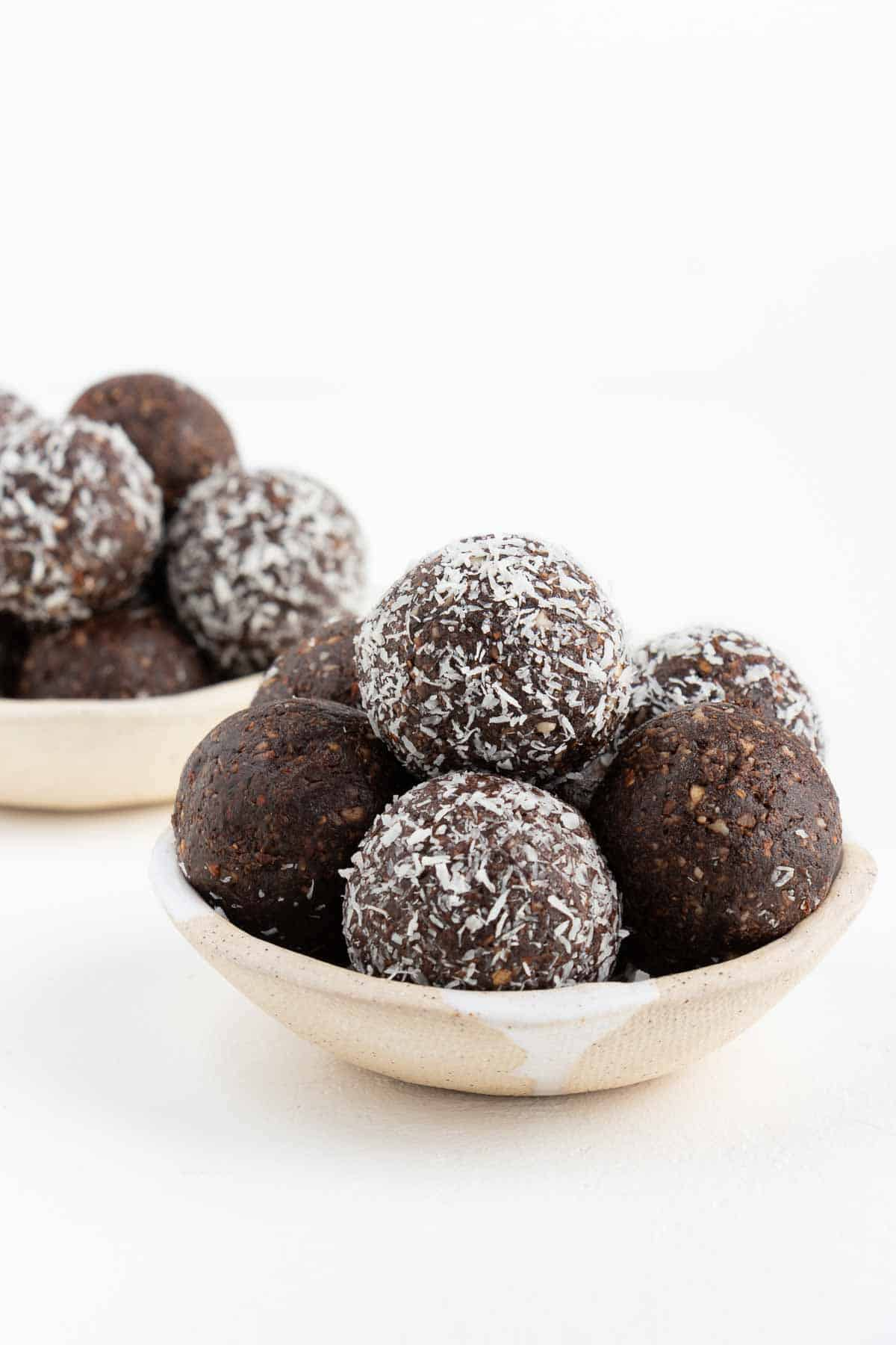 two stacks of coconut chocolate energy balls inside ceramic bowls