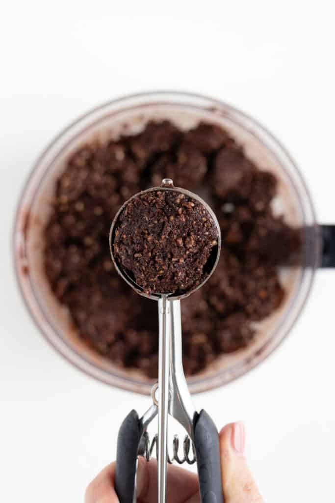a mini cookie scoop containing no bake cacao date dough