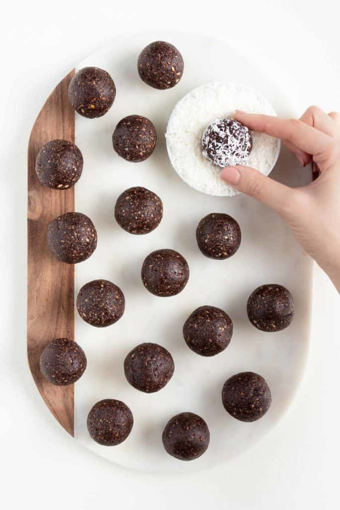 hand dipping a chocolate date ball in coconut