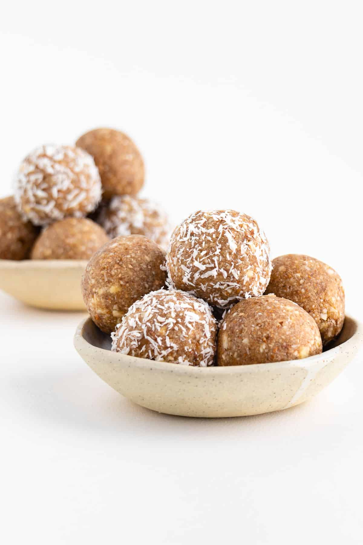 two ceramic bowls filled with coconut almond bliss balls