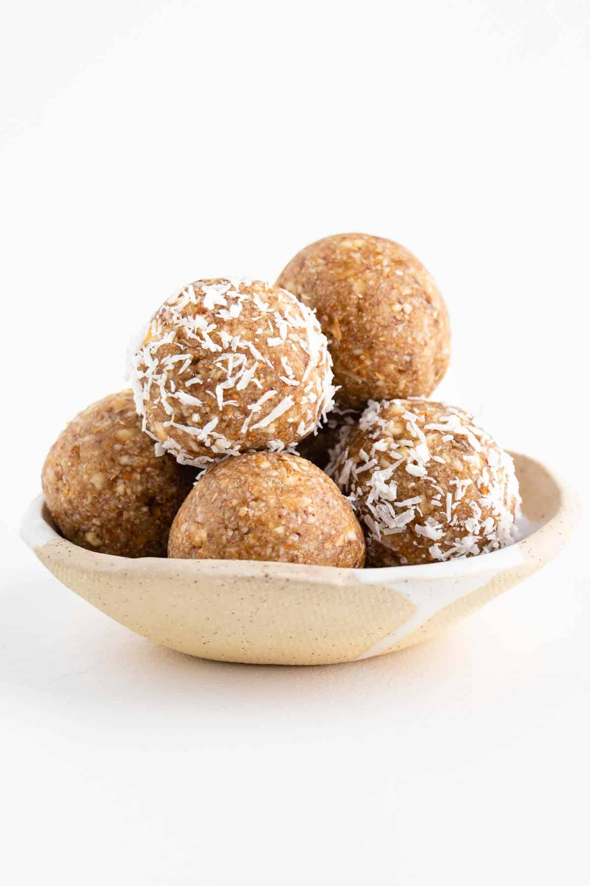 a stack of coconut almond bliss balls in a ceramic bowl