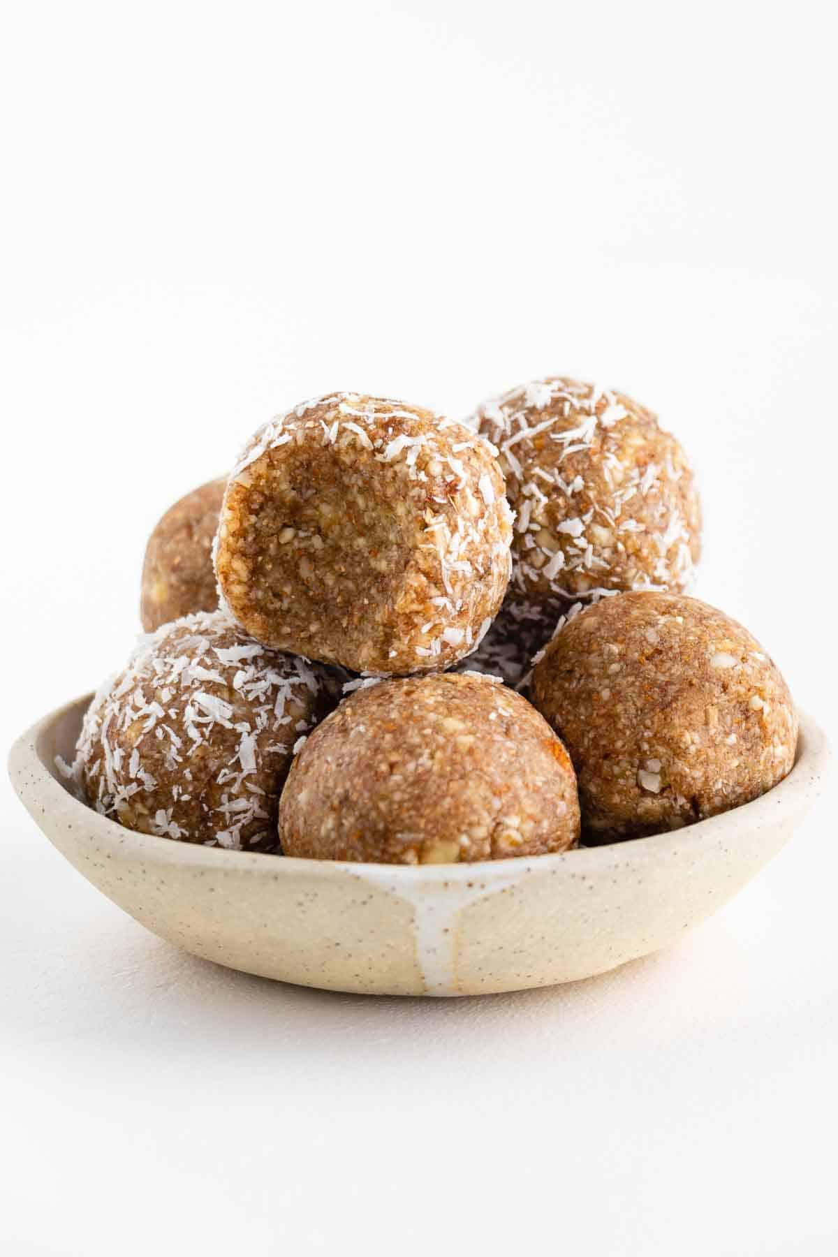 coconut almond bliss balls stacked in a ceramic bowl