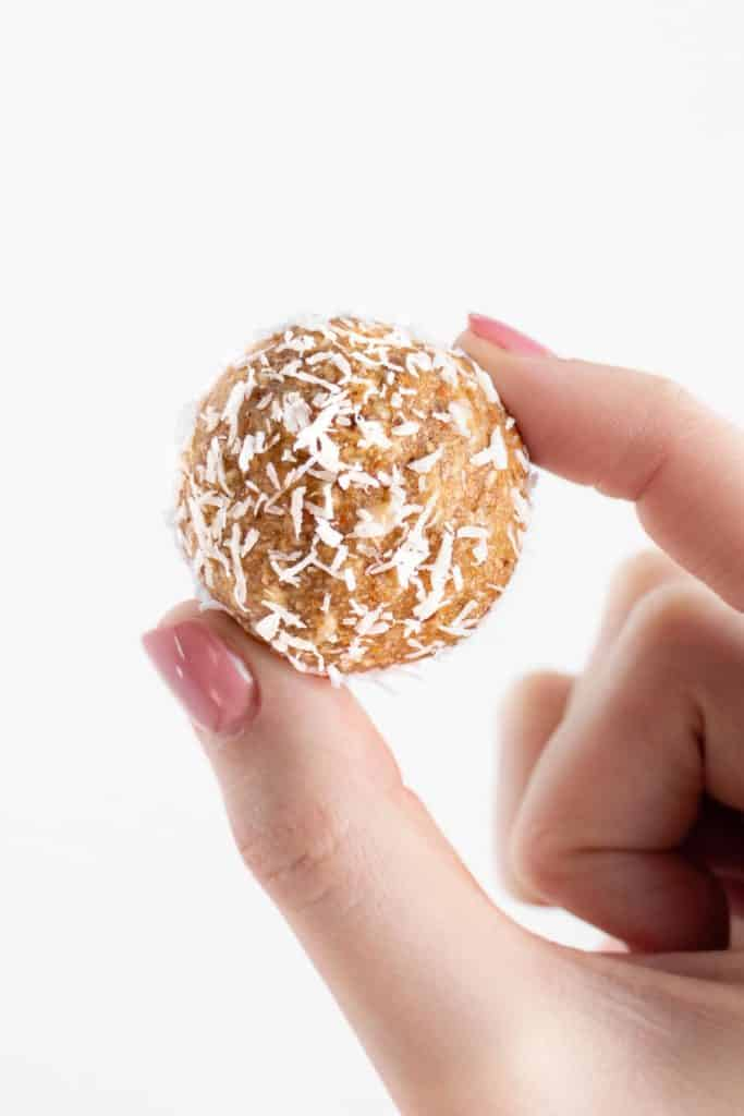 hand holding a coconut almond bliss balls