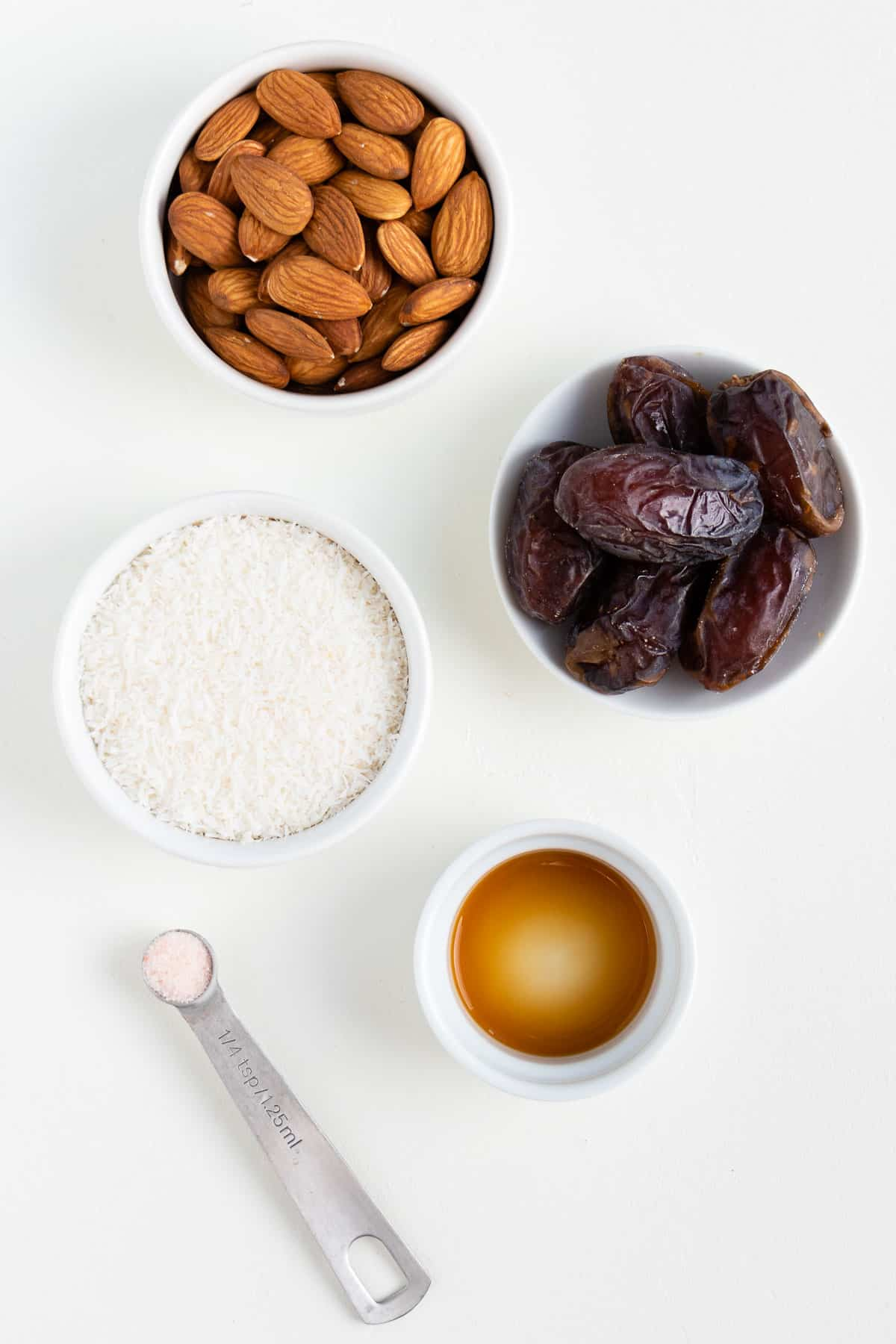 small white bowls of nuts, coconut, dates, and vanilla extract on a white surface