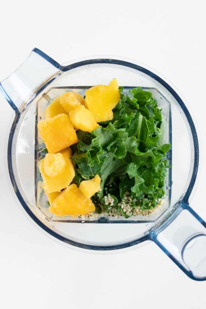 fruit, kale, and hemp seeds inside a blender