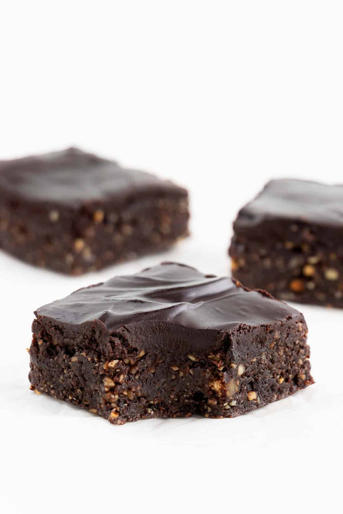three no bake vegan brownies with a bite taken out of the center