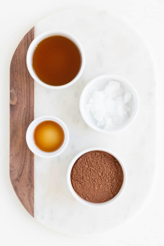 white bowls filled with maple syrup, cacao powder, coconut oil, and vanilla extract on a white marble cutting board