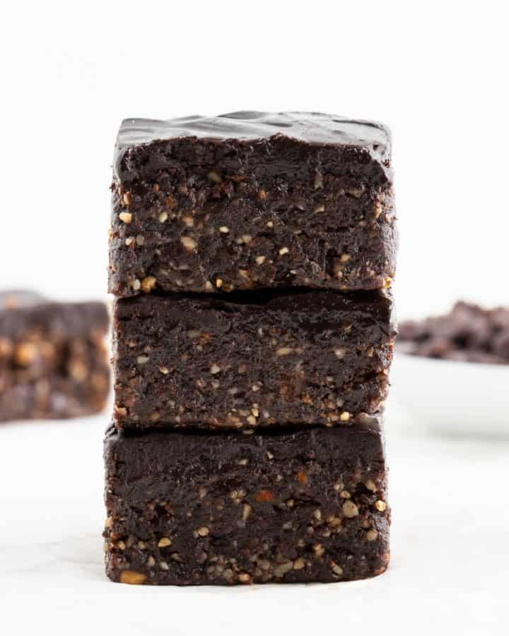 a stack of three no bake vegan brownies with chocolate ganache