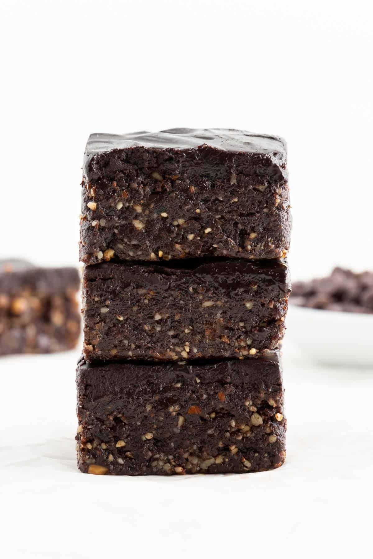 a stack of three no bake vegan brownies with chocolate ganache