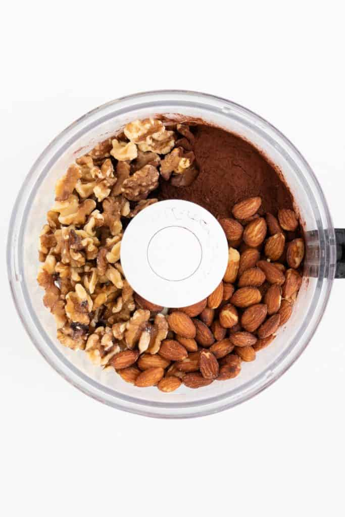 walnuts, almonds, and cacao powder inside a food processor