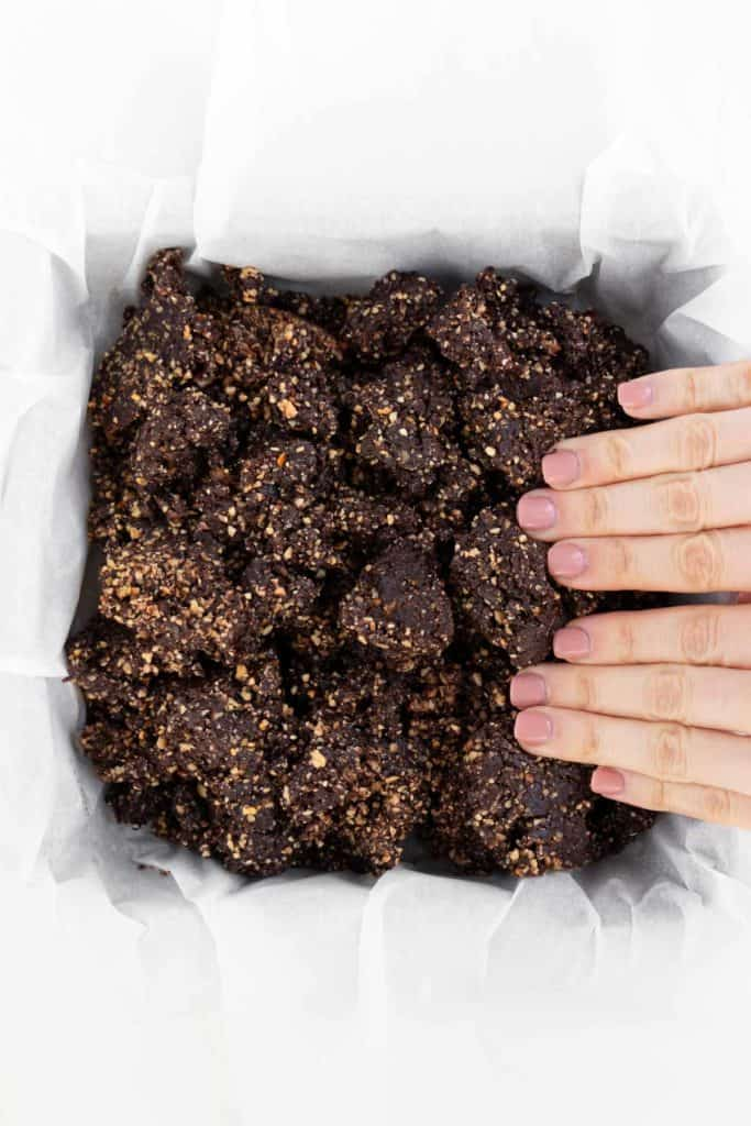 two hands pressing raw vegan brownie dough into a square baking dish