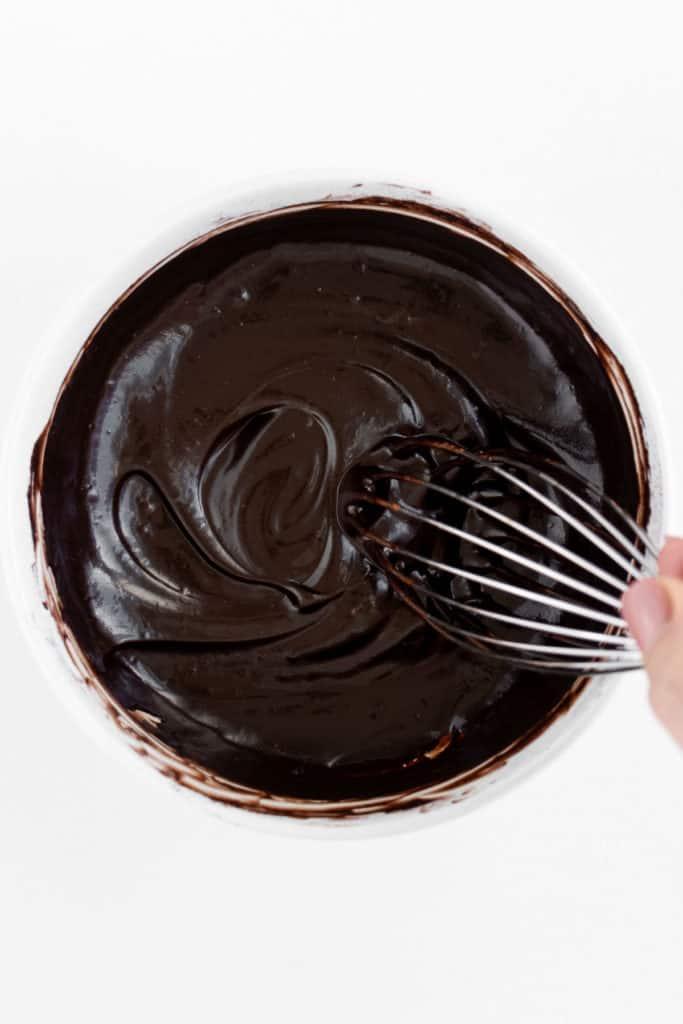 a hand whisking raw vegan chocolate ganache
