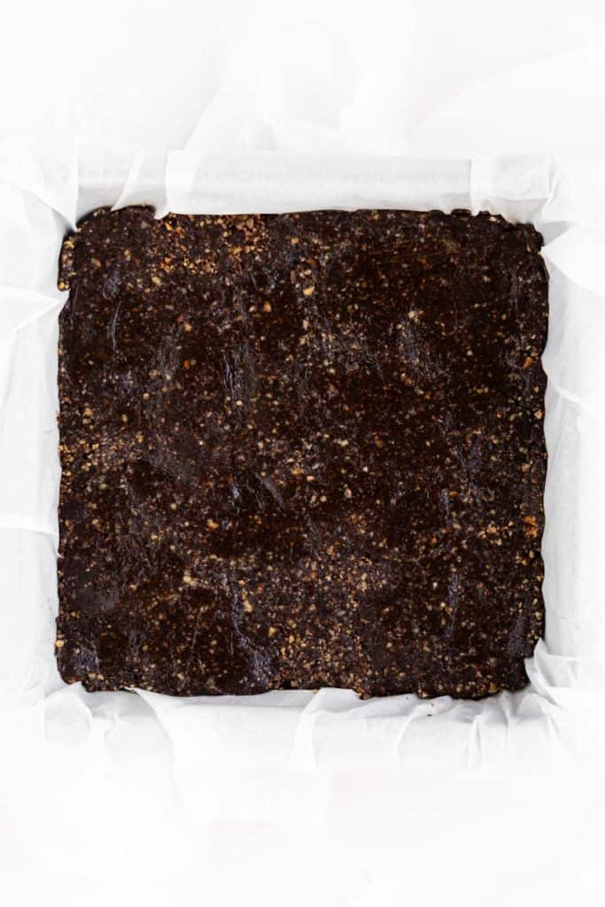 no bake brownie dough pressed into a square baking dish