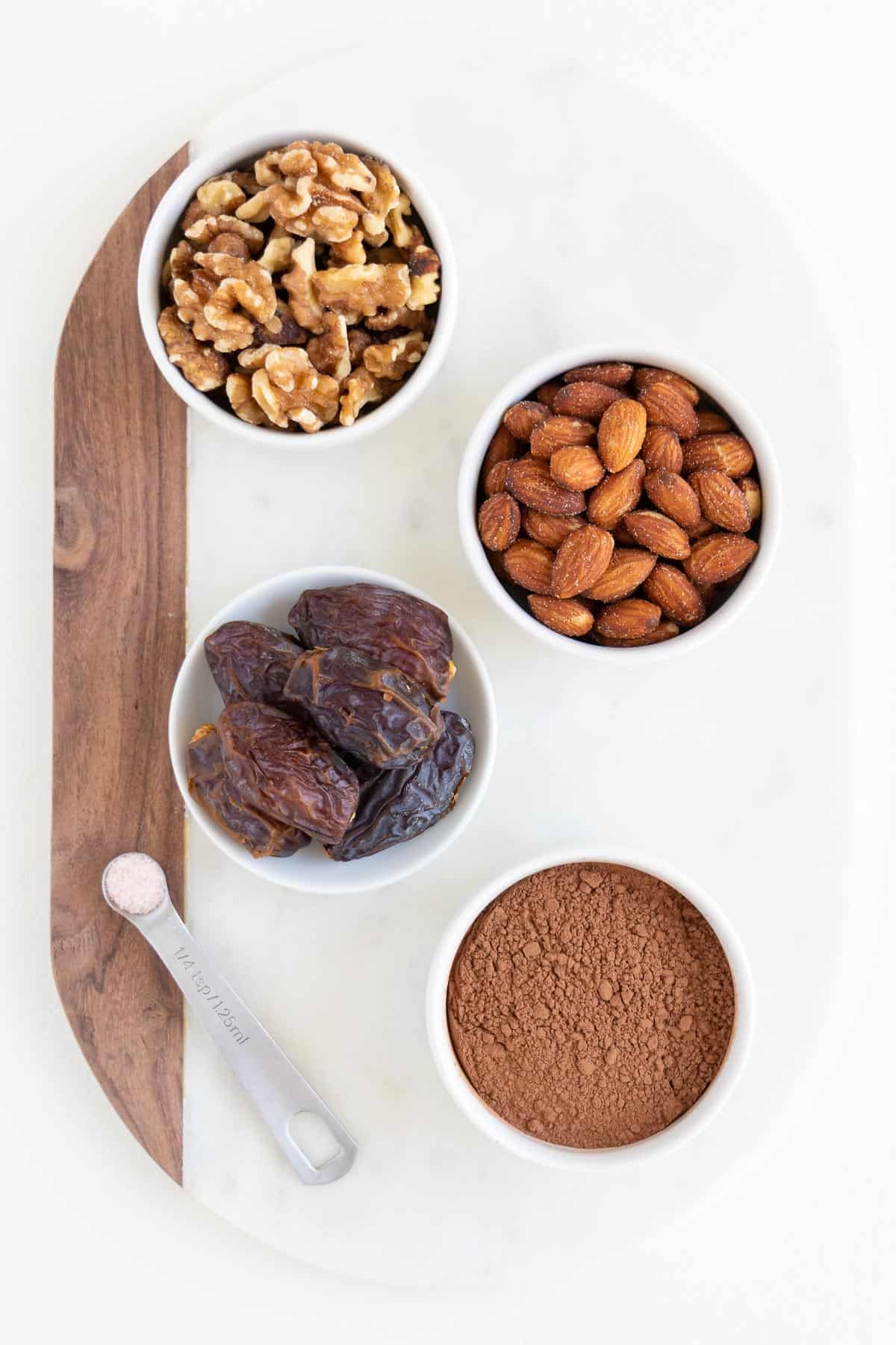 white bowls filled with walnuts, almonds, dates, and cacao powder on a white marble cutting board
