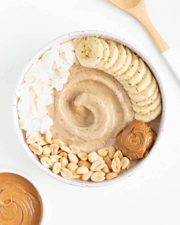 peanut butter banana smoothie bowl beside a bowl of peanut butter and a wooden spoon