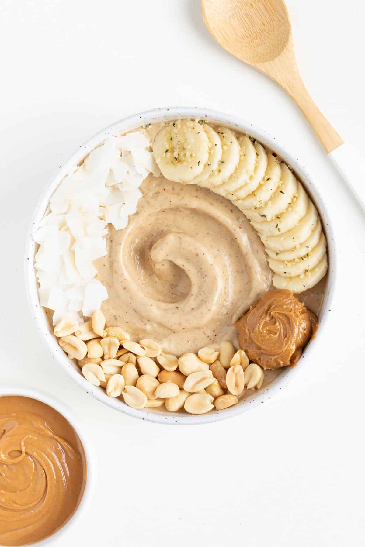 peanut butter banana smoothie bowl next to a small bowl of peanut butter and a wooden spoon