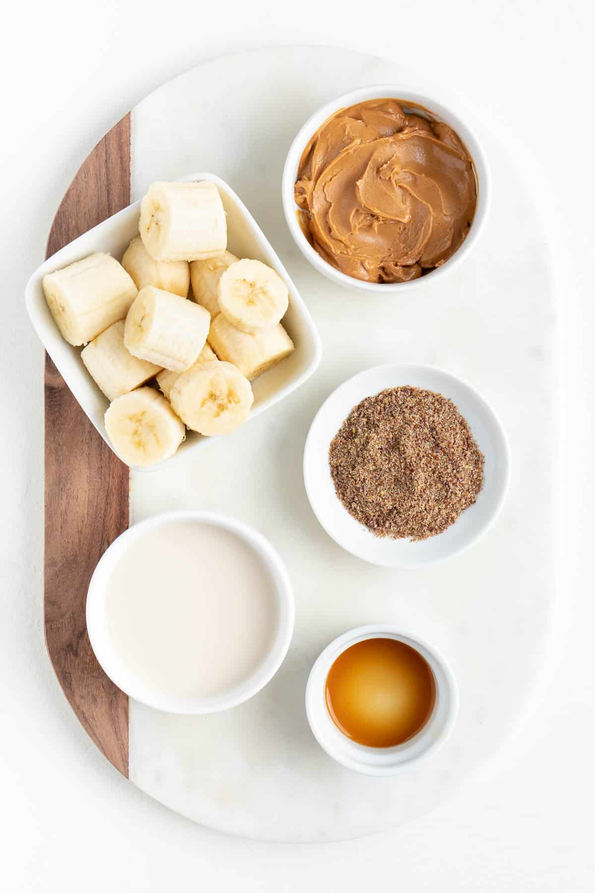 small bowls filled with chopped bananas, flaxseed, vanilla, almond milk, and nut butter on a white marble board