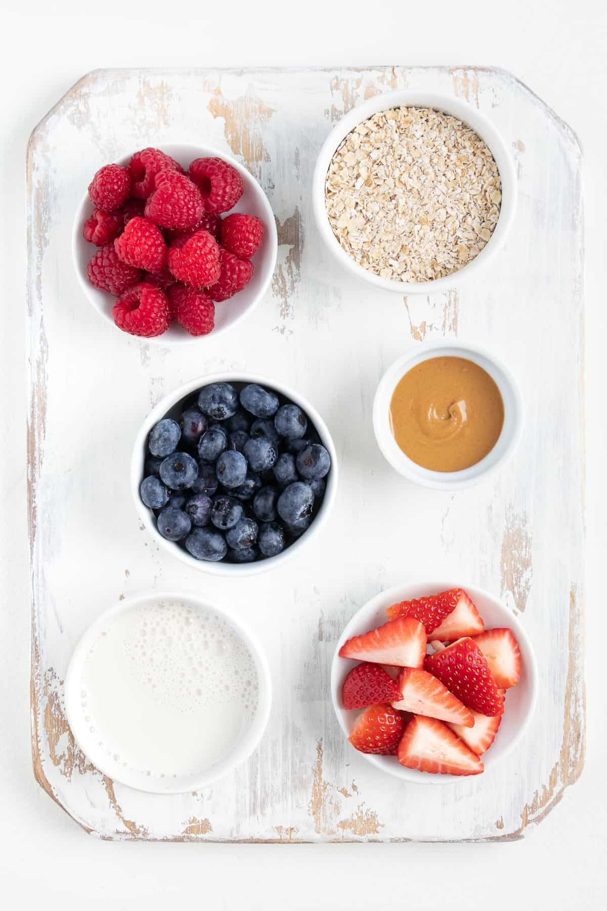 small bowls of raspberries, blueberries, strawberries, milk, oats, and peanut butter
