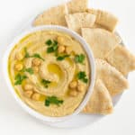 roasted garlic hummus with parsley and chickpeas on top surrounded by sliced pita bread