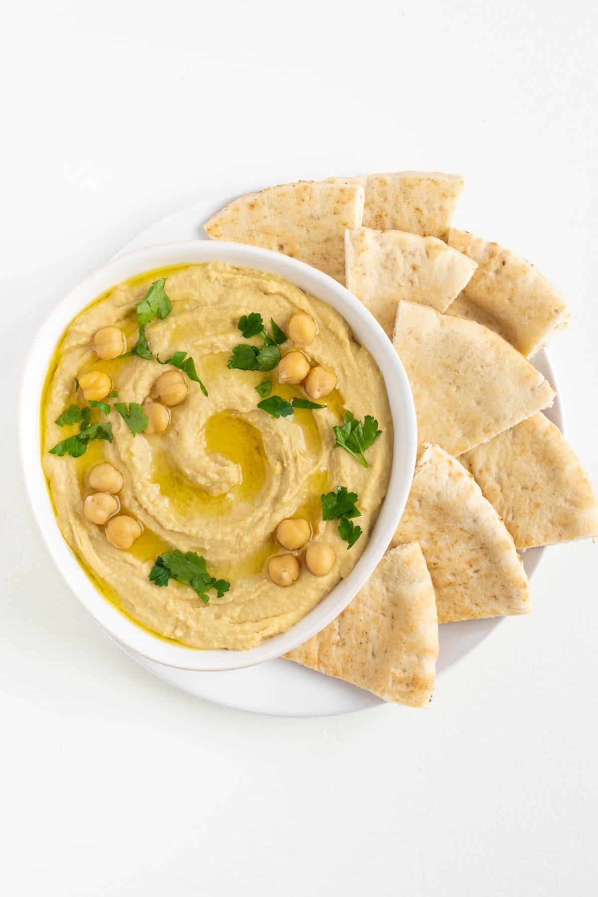 roasted garlic hummus surrounded by sliced pita bread