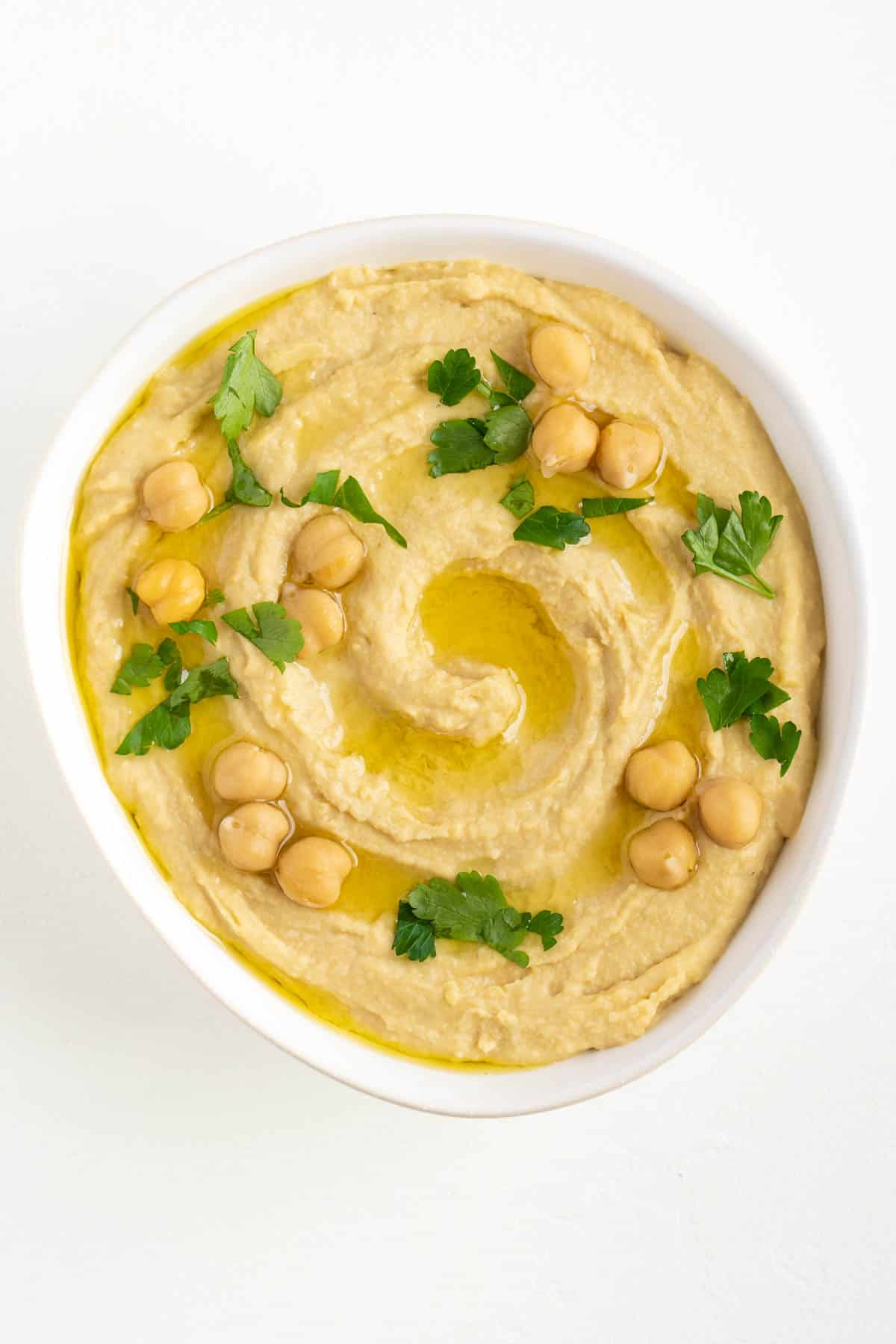 vegan hummus topped with parsley, garbanzo beans, and olive oil