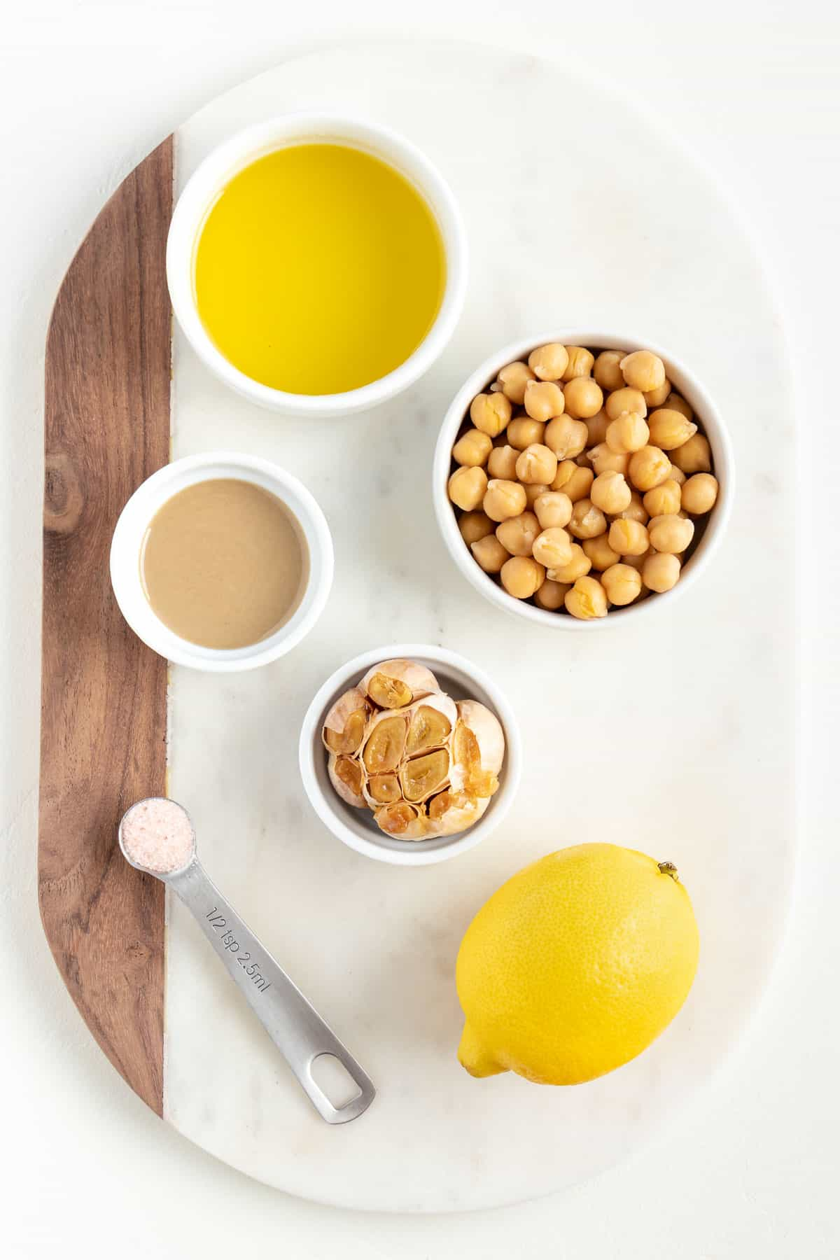 white marble cutting board with small bowls of olive oil, garbanzo beans, roasted garlic, lemon, and tahini
