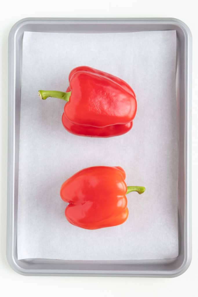 two bell peppers on a baking sheet
