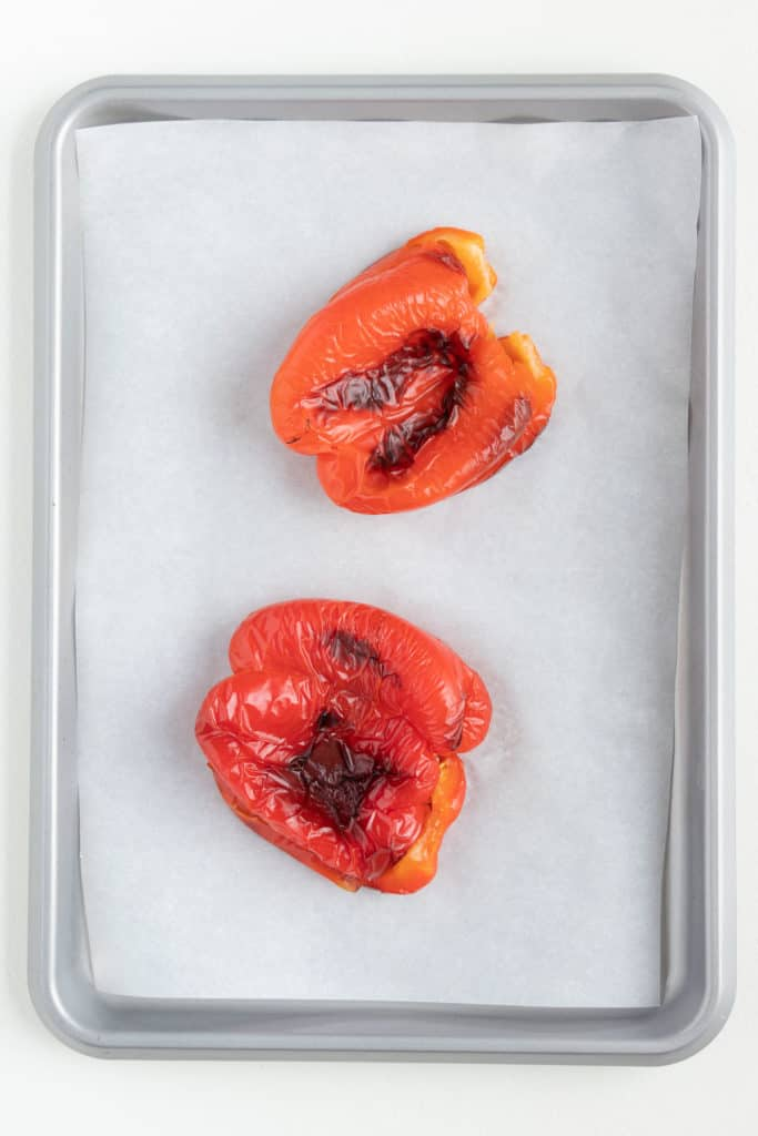 two bell peppers charred on a baking sheet