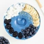 a blue smoothie bowl between a bowl of blueberries and a wooden spoon