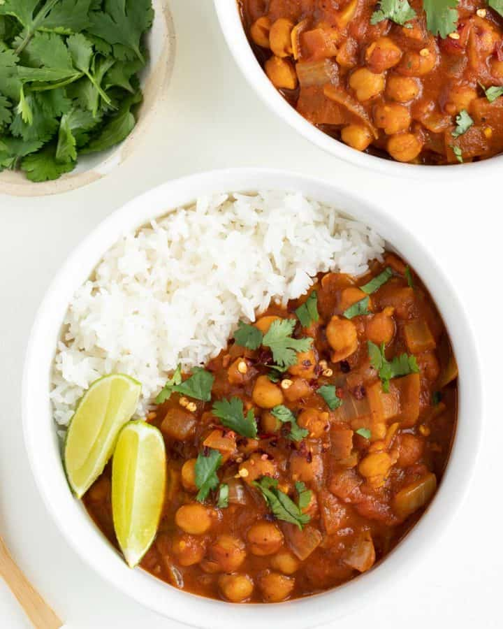 easy chickpea curry and white rice inside a bowl beside a wooden spoon and cilantro