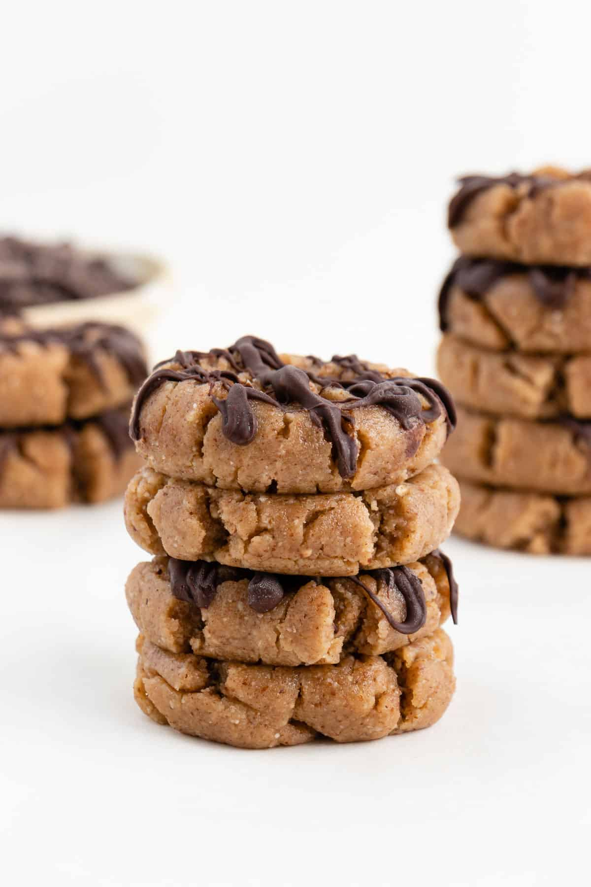 a stack of no bake almond butter cookies in front of a bowl of chocolate chips