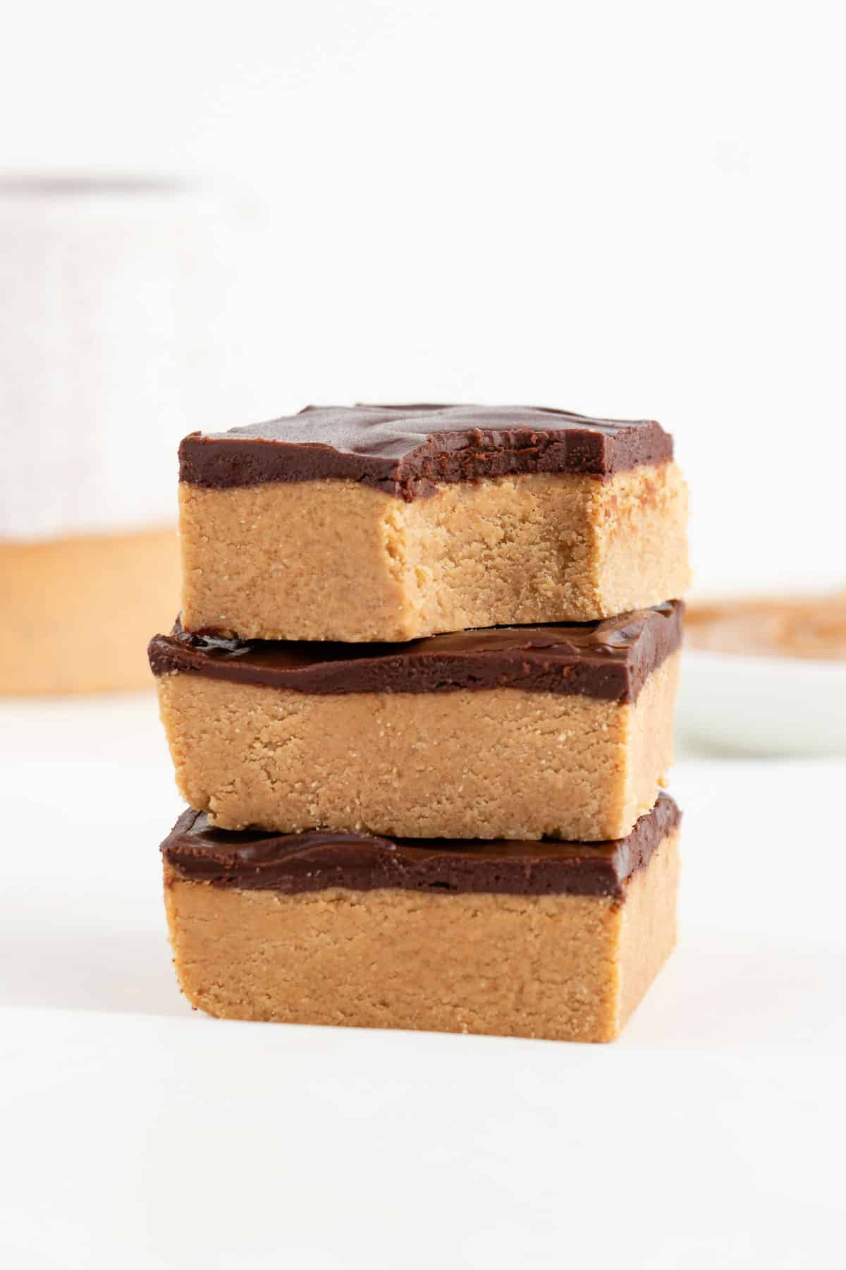 three cacao and nut butter dessert bars stacked with a bite taken out of the top one