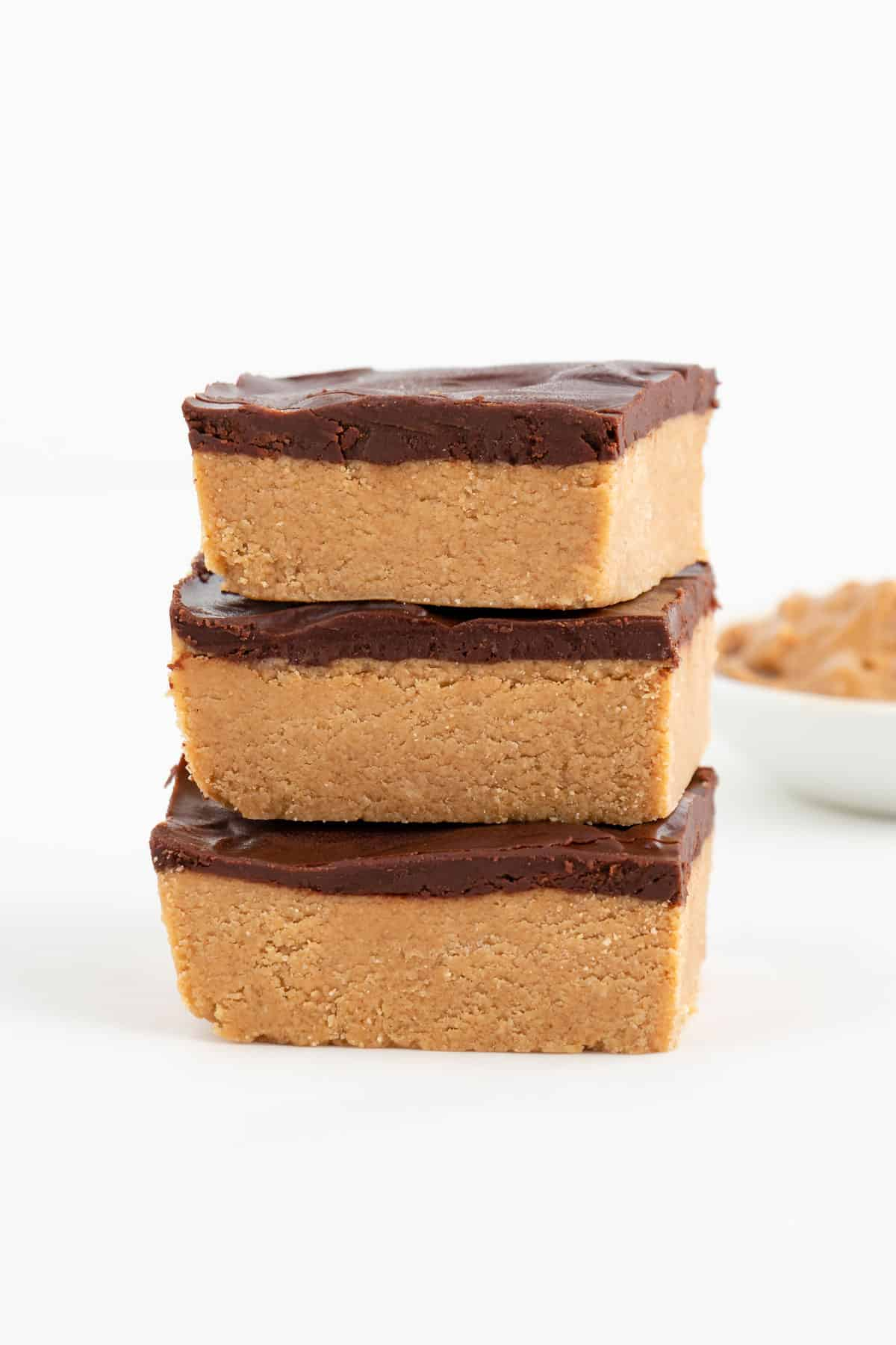 three no bake chocolate peanut butter bars stacked in front of a bowl filled with peanut butter