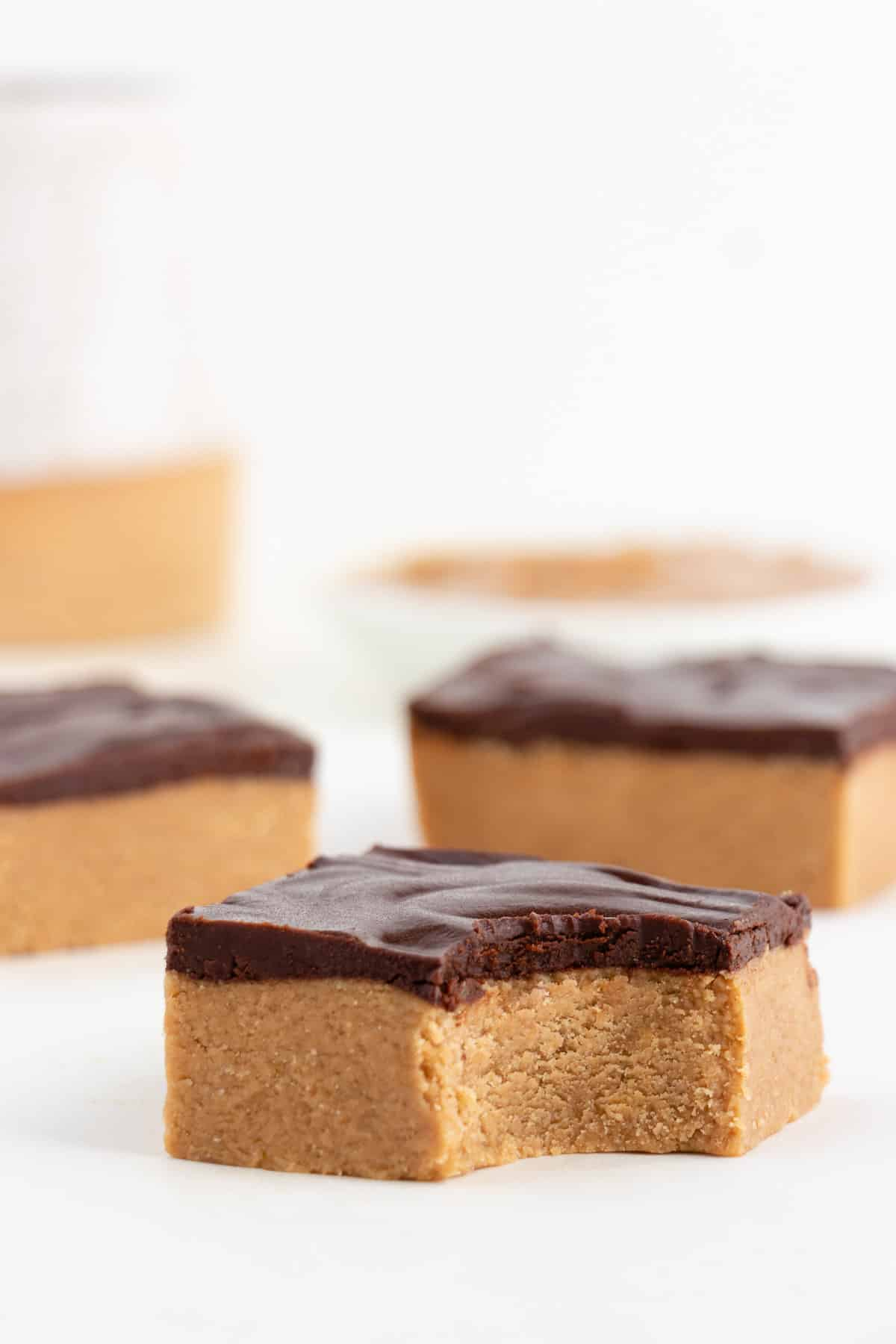 three no bake vegan chocolate peanut butter bars with a bite taken out of the center bar