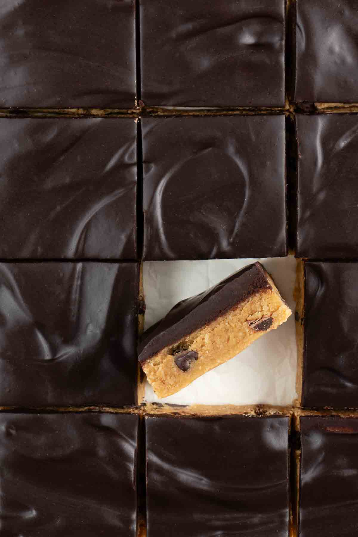 chocolate frosted no bake cookie dough bars sliced into squares with one bar on its side