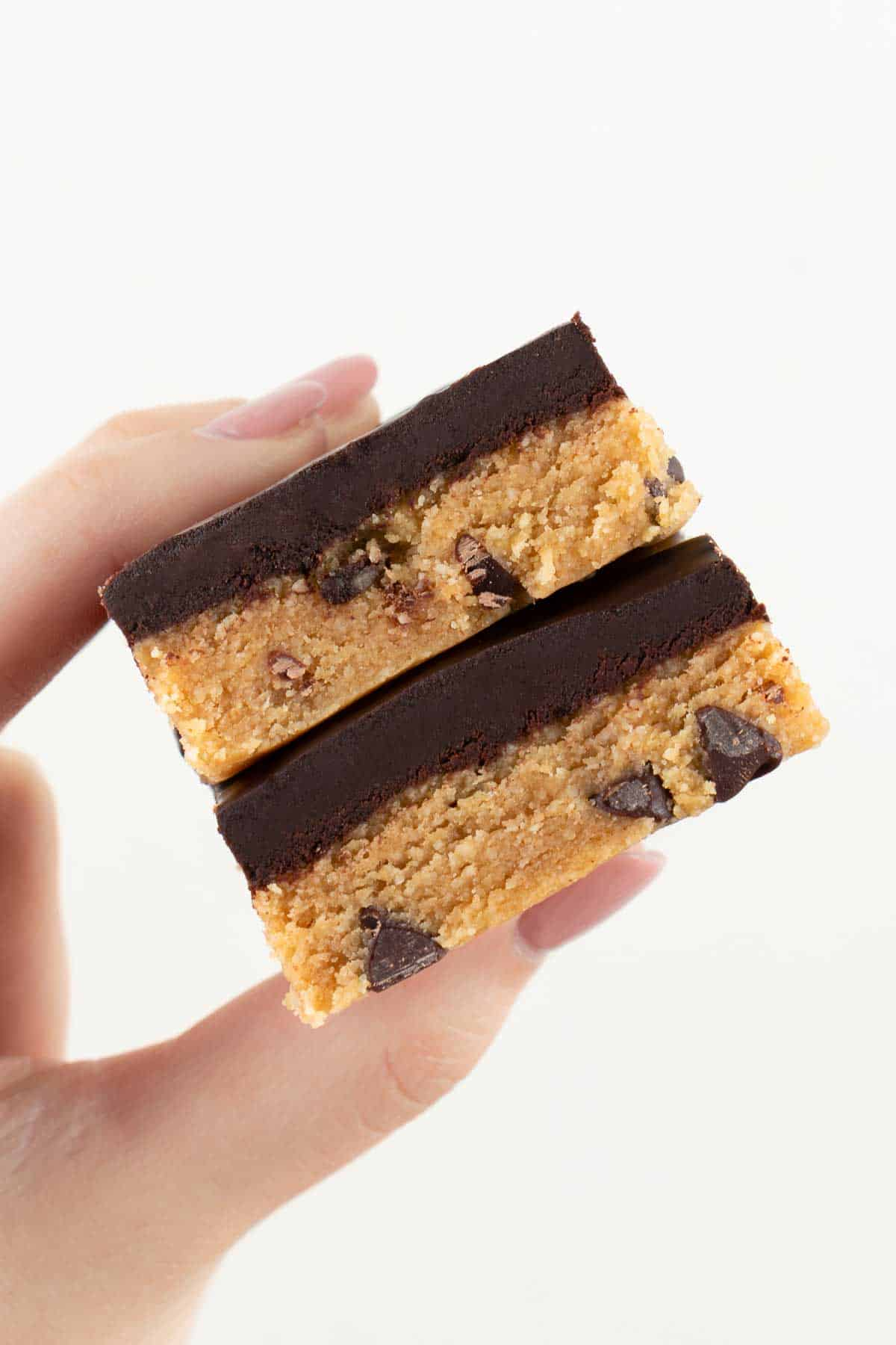 a hand holding a stack of two vegan no bake cookie dough bars
