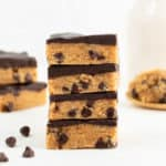 a stack of four no bake cookie dough bars stacked in front of a glass of almond milk and scoop of cookie dough on a wooden spoon